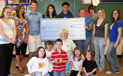 YAC presenting check to students